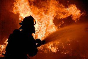 Firefighter extinguishing fire using foam